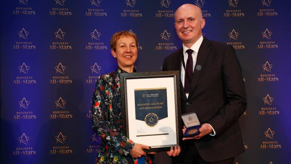 Dr Briga Hynes Presenting Business All-Star Accreditation to Flor McCarthy Managing Partner McCarthy + Co. Specialist Personal Injury and Medical Negligence Solicitors